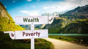 Sinal de rua rico contra a pobreza fotos de stock royalty free