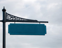 Sinal de rua vazio no cargo do metal, céu nebuloso no fundo fotografia de stock