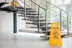 Sinal de segurança com o assoalho molhado do cuidado da frase perto das escadas foto de stock royalty free