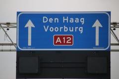 Sinal de sentido com branco para destinos locais a Den Hag e a Voorburg e o limite de velocidade imperativo quando iluminado abai imagem de stock