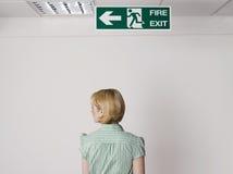 Sinal de Standing Under Exit da mulher de negócios Imagem de Stock Royalty Free