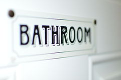 Sinal do banheiro na etiqueta branca da porta Foto de Stock Royalty Free
