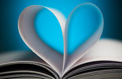 Sinal do coração com as páginas do livro no azul imagens de stock