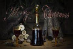 Sinal do Feliz Natal com a garrafa e os vidros do vintage do vinho tinto com referência a Imagem de Stock