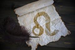Sinal do Leão do zodíaco no papel do vintage com a pena velha na mesa de madeira Fotografia de Stock