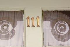 Sinal do número da casa 111 na porta pintada verde Fotos de Stock Royalty Free