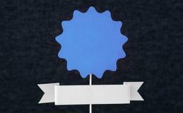 Sinal do papel azul na vara de madeira com fundo escuro Fotografia de Stock Royalty Free