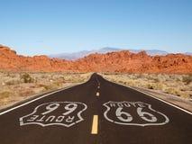 Sinal do pavimento da rota 66 com as montanhas vermelhas da rocha Fotos de Stock Royalty Free