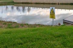 Sinal do perigo visto perto de uma área recentemente escavada da lagoa em um bairro social foto de stock