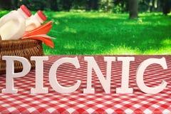 Sinal do piquenique na tabela com cesta e toalha de mesa vermelha Fotos de Stock Royalty Free