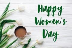 Sinal do texto do dia das mulheres felizes em tulipas e em café em de madeira branco Fotografia de Stock