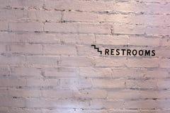 Sinal do toalete em uma parede de tijolo branca Fotos de Stock