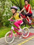 Sinal do trajeto da bicicleta com crianças Meninas que vestem o capacete com mochila Fotos de Stock Royalty Free