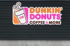 Sinal dos anéis de espuma do ` de Dunkin em uma parede Fotografia de Stock