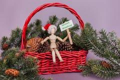 Sinal dos cumprimentos das estações guardado pela boneca de madeira que veste o chapéu de Santa que senta-se na cesta vermelha do fotografia de stock royalty free