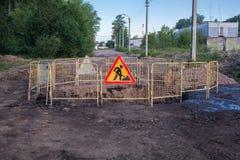Sinal dos trabalhos de estrada no meio da estrada Imagens de Stock Royalty Free