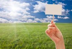 Sinal em branco à disposicão sobre o campo e o céu de grama fotografia de stock