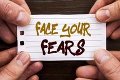 Sinal escrito à mão do texto que mostra a cara seus medos Conceito do negócio para a bravura corajoso da confiança de Fourage do  fotografia de stock