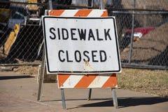 Sinal estando Closed do passeio no passeio na frente da cerca e do equipamento de construção borrados no fundo foto de stock