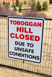 Sinal fechado do monte do Toboggan afixado em um parque público uma vez que toda a neve derreteu fotografia de stock
