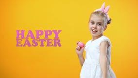 Sinal feliz da Páscoa, menina entusiasmado que joga e que dança com ovos coloridos filme
