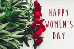 Sinal feliz do texto do dia do ` s das mulheres em peônias vermelhas bonitas no wo branco Imagem de Stock