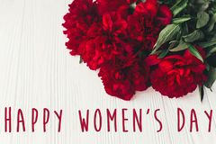 Sinal feliz do texto do dia do ` s das mulheres em peônias vermelhas bonitas no wo branco Fotografia de Stock Royalty Free
