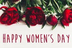 Sinal feliz do texto do dia do ` s das mulheres em peônias vermelhas bonitas no wo branco Fotos de Stock Royalty Free