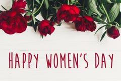 Sinal feliz do texto do dia do ` s das mulheres em peônias vermelhas bonitas no wo branco Imagens de Stock Royalty Free