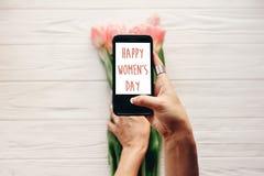 Sinal feliz do texto do dia do ` s das mulheres na tela do telefone gad da terra arrendada da mão Imagem de Stock