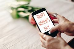Sinal feliz do texto do dia do ` s das mulheres na tela do telefone gad da terra arrendada da mão Fotografia de Stock