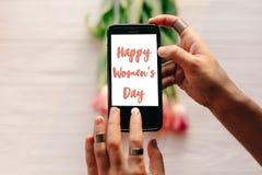 Sinal feliz do texto do dia do ` s das mulheres na tela do telefone gad da terra arrendada da mão Imagens de Stock