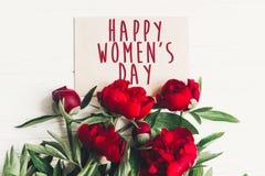 Sinal feliz do texto do dia do ` s das mulheres no cartão do ofício e no peon vermelho bonito Fotos de Stock