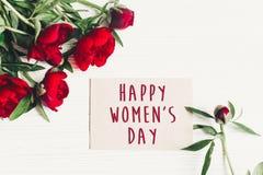 Sinal feliz do texto do dia do ` s das mulheres no cartão do ofício e no peon vermelho bonito Imagem de Stock