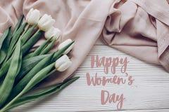 Sinal feliz do texto do dia do ` s das mulheres tulipas brancas à moda no delicado bege Imagens de Stock