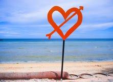 Sinal isolado do cargo com coração vermelho do amor e seta na praia em um fundo azul do mar e do céu no dia de Valentim e no conc Imagem de Stock Royalty Free