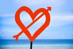 Sinal isolado do cargo com coração vermelho do amor e seta na praia em um fundo azul do mar e do céu no dia de Valentim e no conc Imagens de Stock Royalty Free
