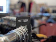 Sinal médio da seção na cremalheira de aço da roupa com os ganchos no armazém fotografia de stock