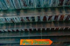 Sinal masculino brilhantemente colorido da seta do banheiro em todos os tampões/letras principais que penduram na corrente suspen imagens de stock royalty free