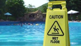 Sinal molhado amarelo do cuidado do assoalho no fundo da piscina no parque da água do divertimento O assoalho molhado do cuidado filme
