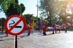 Sinal não fumadores com o parque colorido do equipamento do exercício em público Imagem de Stock