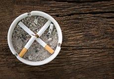 Sinal não fumadores dos cigarros no cinzeiro dos cigarros na madeira Ta imagens de stock