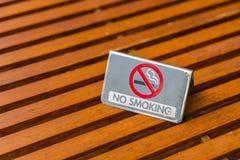 Sinal não fumadores na tabela de madeira Imagens de Stock Royalty Free