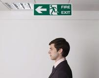 Sinal novo de Standing Under Exit do homem de negócios Imagem de Stock
