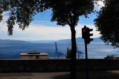 Sinal pedestre vermelho com luz vermelha e árvore com mar e dois guindastes do porto no fundo foto de stock