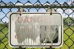 Sinal pintado do perigo em uma cerca imagem de stock