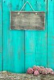 Sinal rústico vazio que pendura na cerca de madeira azul da cerceta antiga com log e beira cor-de-rosa da flor imagens de stock royalty free