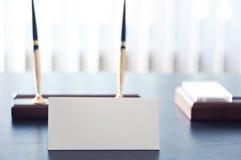 Sinal triangular branco para a etiqueta que está em uma tabela preta Foto de Stock Royalty Free
