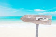 Sinal vazio de madeira com texto 2017, sobre o mar azul borrado Fotografia de Stock Royalty Free