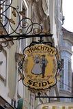 Sinal velho da loja para Trachten Seidl feito do ferro forjado, loja exterior de suspensão em Graz Fotografia de Stock Royalty Free